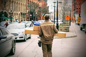 Worker carrying boxes on city street.